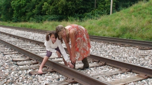 On location filming in Nebraska, at a railroad track (Cecilianna Arriola on left, Madalyn Bowlby on right)